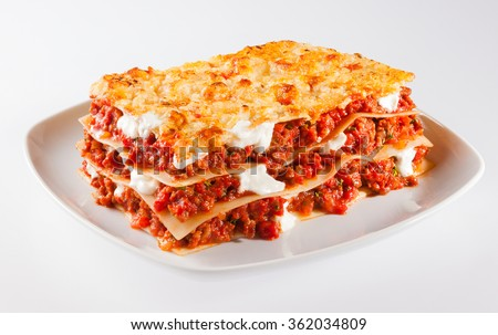 Tasty serving of traditional Italian lasagne with spicy tomato based ground beef and melted mozzarella cheese between layers of noodles - stock photo