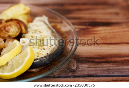tasty shark meat steak with lemon plate and barbecue potato in wooden table - stock photo