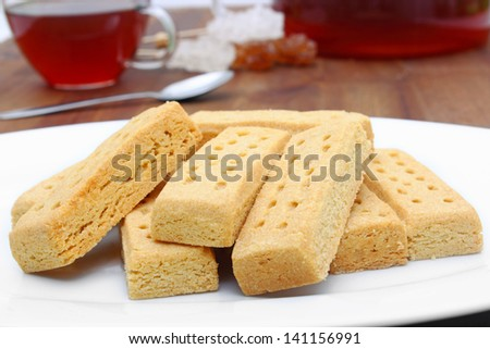 tasty shortbread fingers with black tea. - stock photo