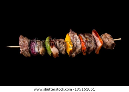 Tasty skewers on black background, close-up. - stock photo