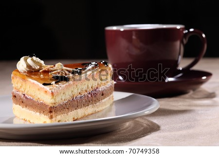 Tasty Slice Of Layered Coffee Cake On A White Plate Along With Cherry Black