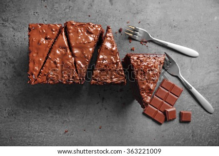 Tasty sliced cake with chocolate and forks on grey background, close up - stock photo