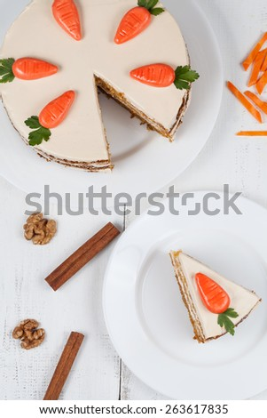 Tasty sliced easter carrot sponge cake with cream and little carrots on white dish background - stock photo