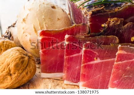 Tasty slices of Italian speck with rosemary - stock photo