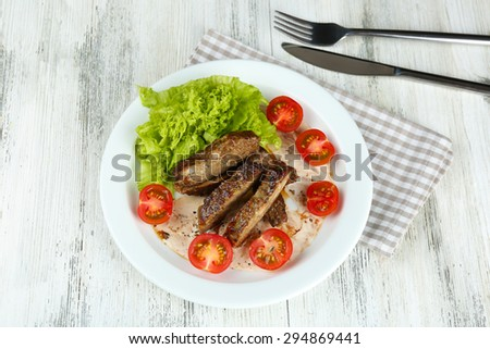 Tasty slices of meat with sauce and cherry tomato on table close up - stock photo