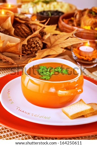 Tasty soup on beautiful decorated table with candles and dry autumnal leaves, festive dinner at home, Thanksgiving day concept - stock photo