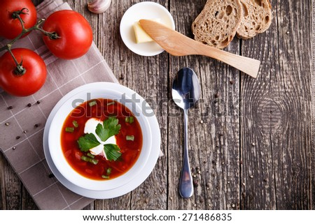 Tasty soup with bread on a wooden background. - stock photo