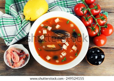 Tasty soup with mussels, tomatoes and black olives in bowl on wooden background - stock photo