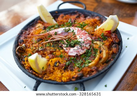 Tasty spanish paella with seafood on a white dish served in restaurant - stock photo