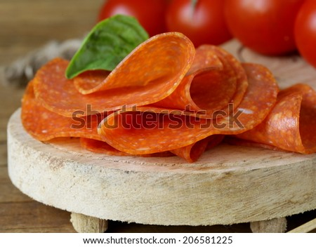 tasty spicy pepperoni sausage on a wooden board - stock photo