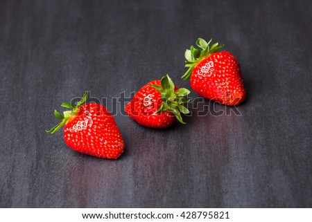 tasty strawberries isolated on black background - stone tile - stock photo