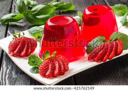 Tasty strawberry jelly and ripe strawberries on plate on a dark wooden table - stock photo