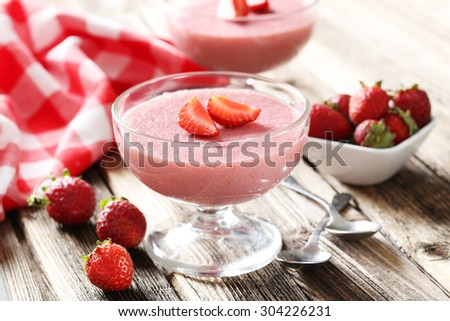 Tasty strawberry mousse in glass on brown wooden table - stock photo