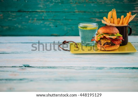 Tasty street food grilled beef burger in crispy shortbread with lettuce and mayonnaise served on small cutting board a rustic wooden table with copyspace - stock photo