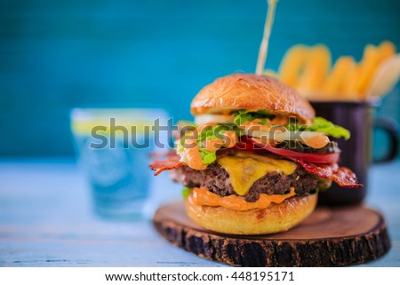 Tasty street food grilled beef burger in crispy shortbread with lettuce and mayonnaise served on small cutting board a rustic wooden table  - stock photo