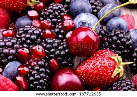 tasty summer fruits on a wooden table. Cherry, Blue berries,  strawberry, raspberries, Blackberries, pomegranate - stock photo