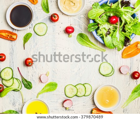 Tasty summer salad and dressing preparation on light rustic background, top view, frame. Healthy lifestyle and vegetarian or diet  food concept - stock photo