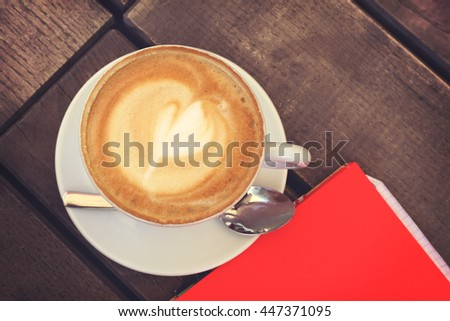 Tasty sweet cappuccino cup with foam on brown wooden table on the summer cafe terrace. Coffee cup on table in the restaurant and notebook with red paper, top view - stock photo