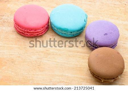 Tasty sweet macaron with wooden texture background.