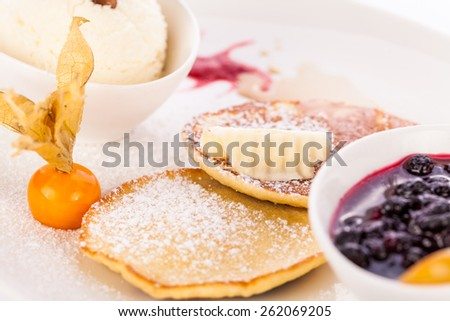 tasty sweet pancakes with vanilla icecream fruit jam and syrup topping - stock photo