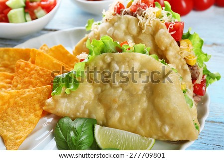 Tasty taco with nachos chips and vegetables on plate on table close up