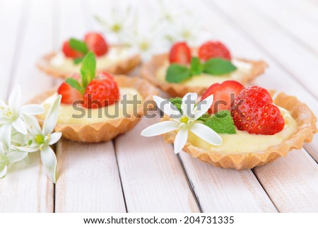 Tasty tartlets with strawberries on table close-up - stock photo