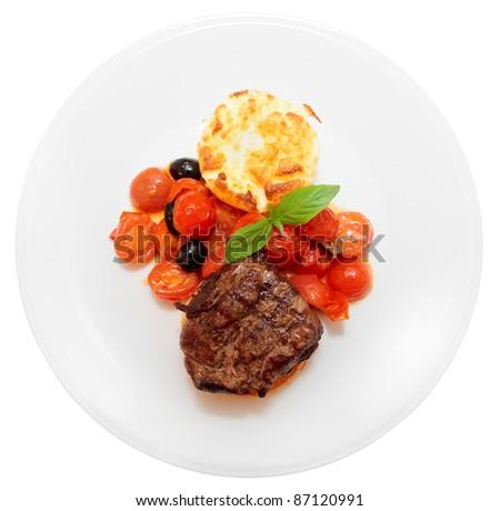 Tasty tenderloin steak with vegetables isolated on white background - stock photo