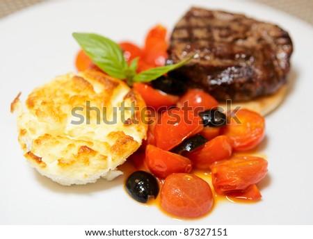 Tasty tenderloin steak with vegetables on plate - stock photo