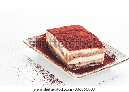 Tasty tiramisu cake with coffee beans on white