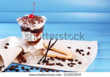 Tasty tiramisu dessert in glass, on color wooden background - stock photo