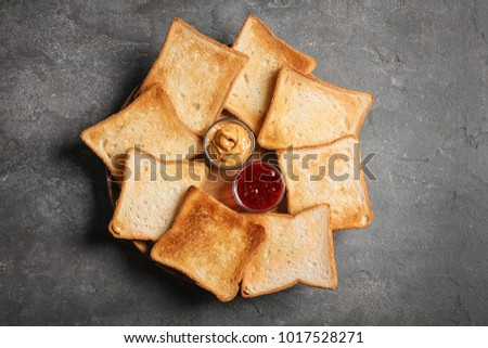 Tasty toasted bread with jam and peanut butter on plate