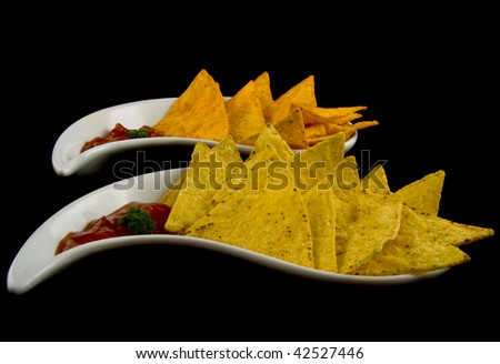 Tasty tortilla chips served on a white plate on a black background - stock photo