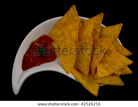 Tasty tortilla chips with salsa on a black background - stock photo