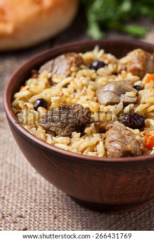 Tasty traditional pilaf meal with rice, fried meat, onion and raisins served in vintage clay bowl on textile table - stock photo