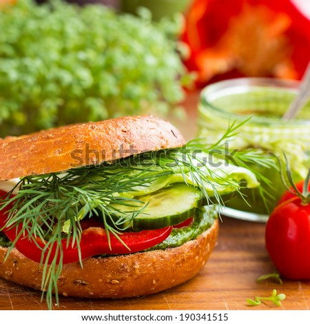 Tasty vegan wholemeal bagel/burger with green pesto, fresh vegetables, and dill. Selective focus. - stock photo