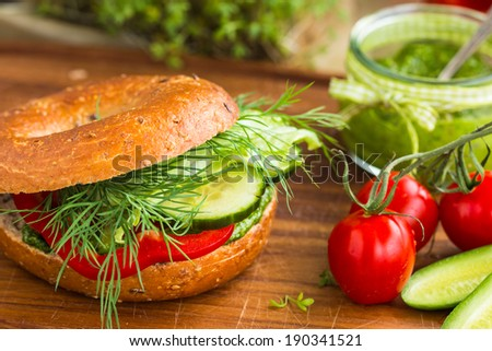 Tasty vegan wholemeal bagel with green pesto, fresh vegetables, and dill. Selective focus. - stock photo