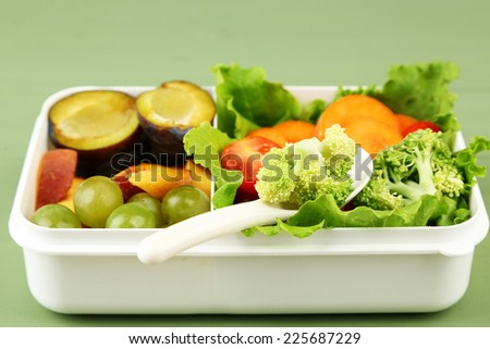 Tasty vegetarian food in plastic box on green wooden table - stock photo