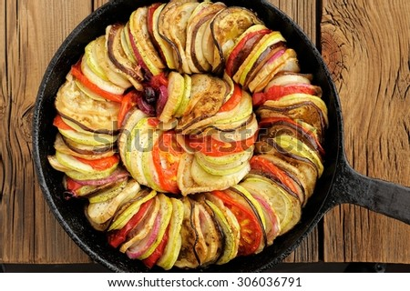 Tasty vegetarian ratatouille made of eggplants, squash, tomatoes and onions in black cast iron pan on wooden table - stock photo