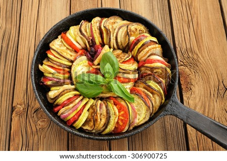 Tasty vegetarian ratatouille made of eggplants, squash, tomatoes and onions in black cast iron pan on wooden table horizontal - stock photo