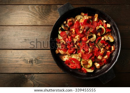 Tasty vegetarian ratatouille made of eggplants, squash, tomatoes and onions in black cast iron pan, on wooden table background - stock photo