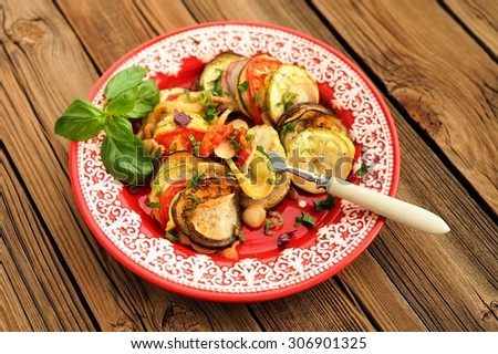 Tasty vegetarian ratatouille made of eggplants, squash, tomatoes and onions with basil in red plate on wooden table horizontal - stock photo