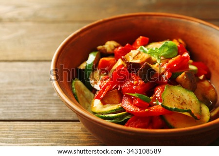 Tasty vegetarian ratatouille made of eggplants, squash, tomatoes in bowl on wooden table background - stock photo