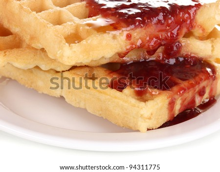 Tasty waffles with jam on plate close-up isolated on white