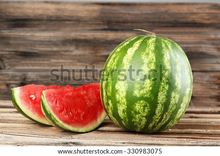 Tasty watermelon on brown wooden background - stock photo