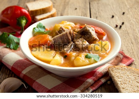 Tasty winter stew with meat and vegetables in bowl with ingredients over rustic wooden table - stock photo