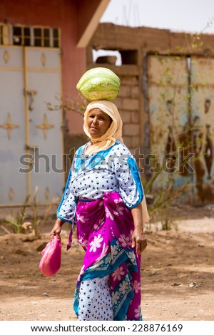 TATA, MOROCCO, AUGUST 30: Unidentifed Moroccan woman carrying a watermelon on her head in the city of Tata and wearing the traditional Moroccan clothes. Morocco 2014. - stock photo