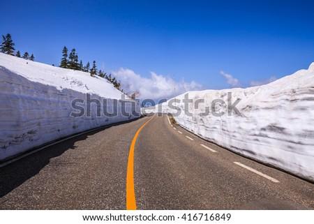 TATEYAMA, JAPAN - Apr 15, 2016: Unidentified tourists walk along snow corridor on Tateyama Kurobe Alpine Route, Japanese Alp in Tateyama, Japan - stock photo