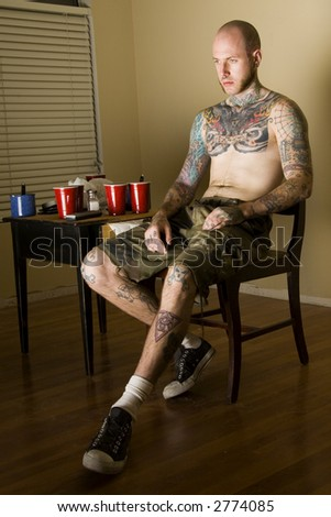 Tatooed male watching TV - stock photo