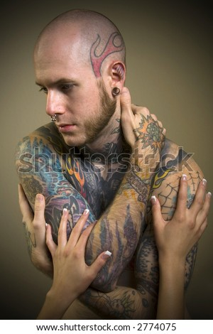 Tatooed Male with a female's hands touching his ink - stock photo