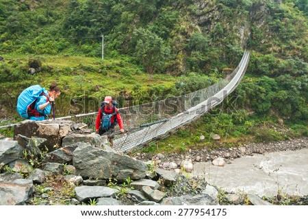TATOPANI, NEPAL - OCTOBER 04, 2012 - Girl tourist crossing the river Kali Gandaki on a suspension bridge, accompanied by Nepalese guide - stock photo